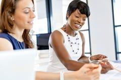 Kvinnor som tillsammans arbetar, kontorsinre royaltyfri fotografi