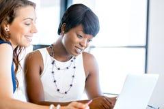 Kvinnor som tillsammans arbetar, kontorsinre royaltyfri foto