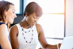 Kvinnor som tillsammans arbetar, kontorsinre arkivbild