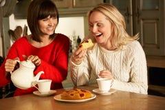 Kvinnor som tillsammans tycker om Tea och caken Fotografering för Bildbyråer