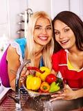 Kvinnor som tvättar frukt på kök. Arkivbilder