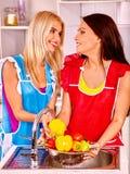 Kvinnor som tvättar frukt på kök Arkivfoto