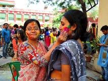Kvinnor som tycker om den färgrika festivalen av Holi Arkivbild