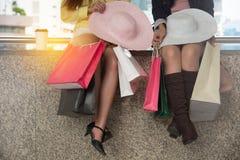 Kvinnor som tycker om helgen som shoppar och tar en vila arkivbild