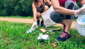 Kvinnor som upp väljer avfall som gör plogging royaltyfria foton
