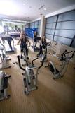Kvinnor som ut fungerar på rotering, cyklar på idrottshallen Arkivfoto