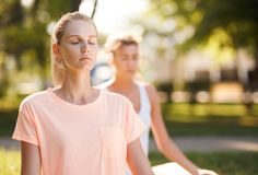 Kvinnor som utomhus gör yoga på soluppgång Morgonmeditation arkivbilder