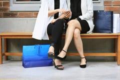 Kvinnor som utomhus sitter med shoppingpåsar och använder smarta telefoner royaltyfria foton