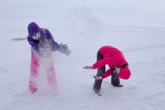 Kvinnor spelar i snön under ett snöfall på isen av sjön Baik Arkivfoto