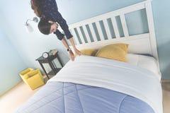 Kvinnor svävar ut mot gravitation av hennes säng som önskar att gå att bädda ned arkivbild