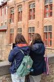 Kvinnor tar bilder på gatan av Bruges Arkivbilder