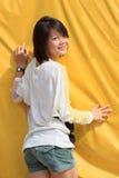 Kvinnor tar en stolpe för fotografi med gula plas Royaltyfri Foto