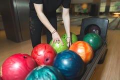 Kvinnor väljer en bowlingklot Välja färgade bollar för att bowla arkivfoto