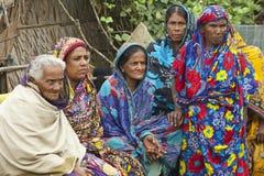 Kvinnor väntar på deras maker från fiske i Mongla, Bangladesh Arkivfoto