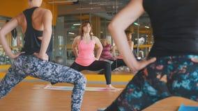 Kvinnor visar yogaövningar för kvinnor i konditionklubba Arkivfoto