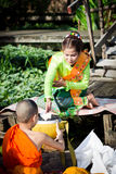 Kvinnorna i thailändsk klänning ger allmosa till munkar i Ladkrabang, Bangkok, Thailand Royaltyfri Foto