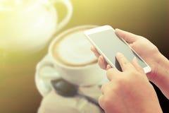 Kvinnorna som använder den smarta telefonen på coffee shop Arkivbilder