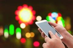 Kvinnorna som använder den smarta telefonen på den suddiga ljusa gatan Arkivfoto