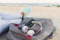Kvinnors ben i jeans och gymnastikskor, ryggsäck, hörlurar och sma Arkivfoto