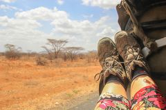 Kvinnors ben och turist- kängor på bakgrunden av afrikanen royaltyfri fotografi