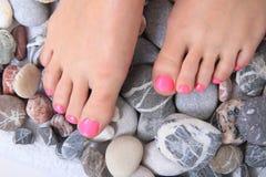 Kvinnors ben (spikar) och stenar (pedikyren) Arkivfoto