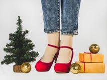 Kvinnors ben, stilfulla skor, gåvor med ett rött band royaltyfri fotografi