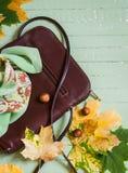 Kvinnors brun läderhandväska, siden- halshalsduk och gulinglönnlöv Arkivbilder