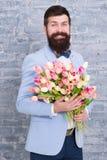 kvinnors dag Blomma f?r mars 8 abstrakt f?r?lskelse f?r blommor f?r f?gelpardatum Internationell ferie Sk?ggig man med tulpanbuke royaltyfri foto