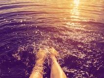 Kvinnors fot plaskade havsvatten på solnedgången royaltyfri foto