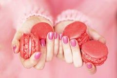 Kvinnors händer med en härlig rosa manikyr Arkivbild