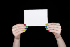 Kvinnors händer med kulört spikar att rymma ett vitt ark av papper Arkivbild