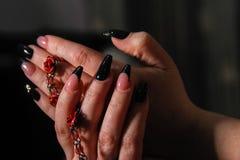 Kvinnors händer med spikar konster på spikar att rymma dräktsmycken arkivfoton