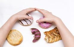 Kvinnors händer, några donuts med isläggning och pajer på en vit yttersida, sötsaker, mat fotografering för bildbyråer