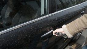 Kvinnors händer och tangent försöker att öppna dörren av hans smutsiga svarta bil lager videofilmer