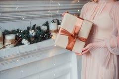 Kvinnors händer som rymmer en gåva i Kraft papper Julfilial och klockor royaltyfri fotografi