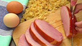 Kvinnors händer som skivar grisköttbacon, en ingrediens för att laga mat lager videofilmer