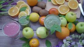Kvinnors händer tar ett exponeringsglas med en smoothie på köksbordet med ny frukt banta sunt stock video