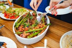Kvinnors händer traver sig ett mål i en platta av lunch Begreppet av näring bufferten Mat matställe Begreppet av att dela royaltyfria foton