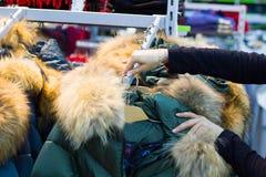 Kvinnors händer trycker på hängarna med varma omslag i boutique arkivfoto