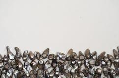 Kvinnors halsband av gråa rå flodpärlor på vit bakgrund royaltyfria foton