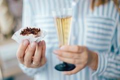 kvinnors hand som rymmer ett exponeringsglas av champagne på bakgrunden av den festliga tabellen arkivfoton