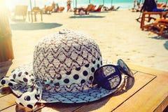 Kvinnors hatt och solglasögon ligger på en trätabell på en solig sandig strand vid havet arkivbilder