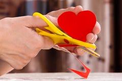 Kvinnors händer som klipper pappers- hjärta för valentin dag Arkivfoto