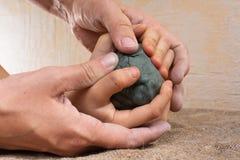 Kvinnors händer som vägleder händer för ett barn för att hjälpa honom att arbeta med rå lera Arkivfoton