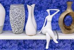 Kvinnors keramiska statyett på en hylla med vaser arkivfoto