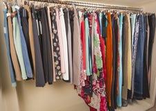 Kvinnors kläder som hänger på stången Arkivfoto