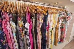 Kvinnors kläder som hänger på stången Arkivbilder