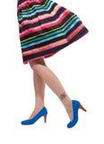 Kvinnors mångfärgade klänning och ben i blåa höga häl Royaltyfri Foto
