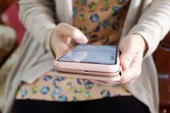 Kvinnors mobiltelefon för handinnehav som smsar, messagingkommunikation royaltyfri bild