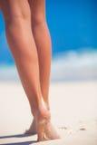 Kvinnors sätter på land härliga släta ben på vit sand arkivfoton